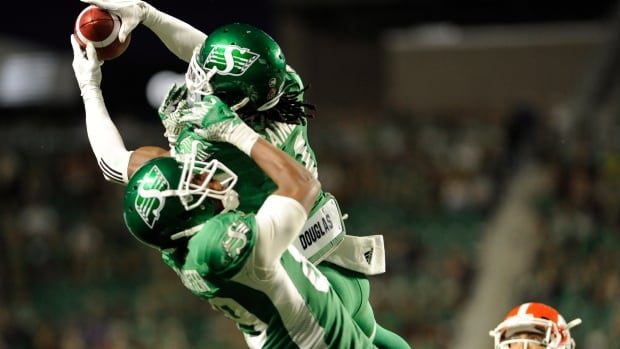 Saskatchewan Roughriders defensive back Ed Gainey outleaps teammate Duron Carter to record his fourth interception during the second half on Aug. 13, 2017.
