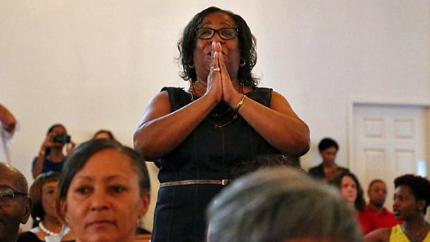 Sheltina Anderson stands up to pray during Sunday service at the Mt. Zion First African Baptist Church in Charlottesville, Va., a day after a rally led by white nationalists left a woman dead and numerous people hurt. 'The Charlottesville here on TV is basically the Charlottesville you see,' she said. 'Nothing has changed.'