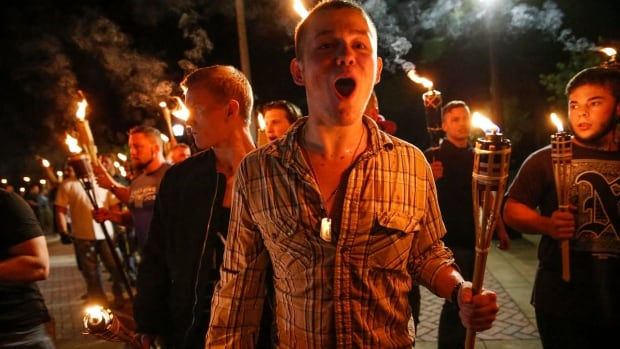 White nationalists march with torches through the University of Virginia campus in Charlottesville, Va., on Saturday.  A website created Sunday is dedicated to collecting the names, social media profiles, colleges and employers of people photographed at the rally, where violence erupted over the weekend.
