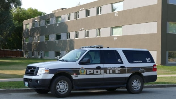 A police vehicle sits outside an apartment block where police found the 20th homicide victim in Winnipeg so far in 2017.