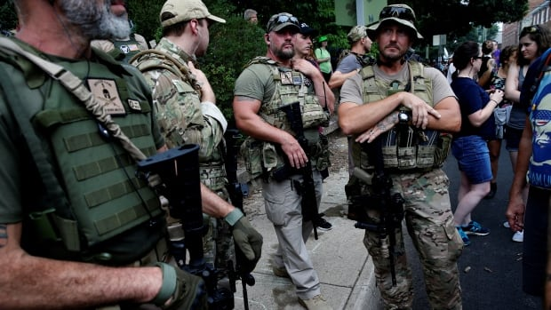 Militia members stand near a rally in Charlottesville, Va. Virginia's governor said they had better equipment than the state police.