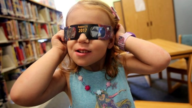 Eclipse glasses, like this real pair being sported by a three year old in North Carolina, are in high demand in advance of the Aug. 21 solar eclipse.