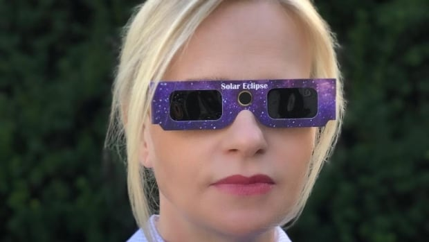 Vancouver realtor Candace Rohrick in the glasses she had been giving away to watch the solar eclipse, before realizing they could be fake.