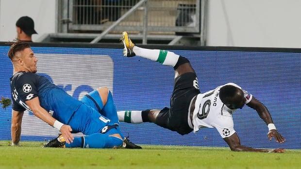 Liverpool's Said Mane is taken down by Hoffenheim's Ermin Bicakcic during their Champions League qualifier Tuesday in Sinsheim, Germany.