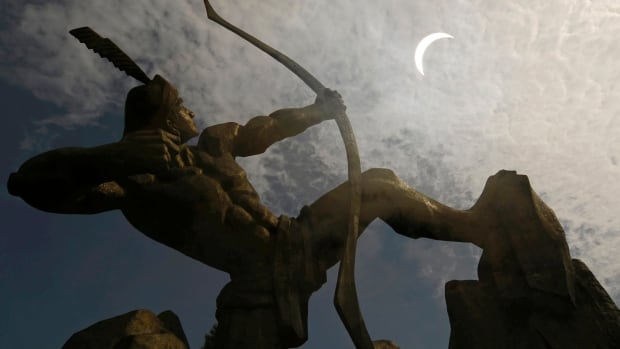 A statue of Houyi, a Chinese legendary hero who shot down nine suns with his bow and arrow, is silhouetted against a partial solar eclipse in the Shanxi province on July 22, 2009.