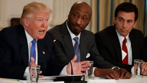 U.S. President Donald Trump ended two business advisory panels after a number of high profile defections on Wednesday. One of the panel members was Merck CEO Kenneth Frazier, centre, before he resigned yesterday.