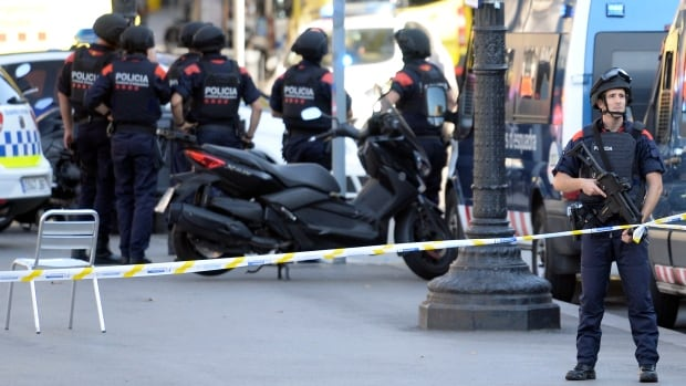 Armed policemen stand in a cordoned off area after a van ploughed into the crowd, killing 13 and injuring dozens in Barcelona, Thursday. Canadians in the city are being urged to stay away from tourist areas.