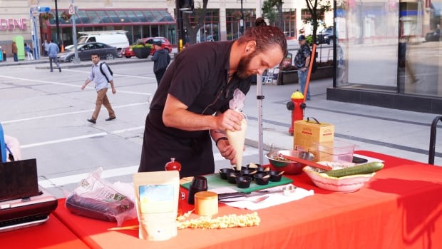 Chef Beau Schell from the Merchant Kitchen delicately plates samples of his Manitoba produce-inspired tabbouleh salad.
