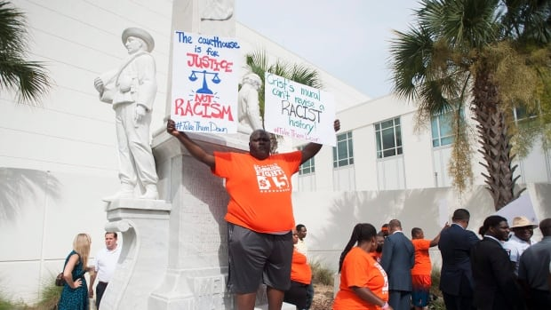 "Marc Rodriguez, a member of the ""Florida Fight for $15"" organization stands in protest along with other activists to have a Confederate monument removed at the old Hillsborough County Courthouse in Tampa, Fla. Sports teams have banded together to dedicate funds to help in the removal of the statue."