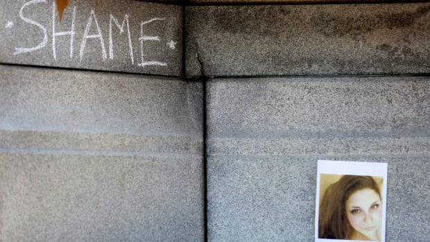 The word 'shame' is written on a Confederate monument in Norfolk, Va., near a photograph of Heather Heyer, who was killed Saturday in Charlottesville, Va. Naming-and-shaming campaigns online are targeting participants in the rally where she was killed.