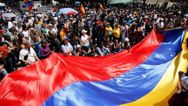 Anti-government demonstrators wave a Venezuelan flag during a protest against Venezuela's President Nicolas Maduro in Caracas on Aug. 12. The country's new constitutional assembly approved a decree Friday to give it power over the opposition-led congress.