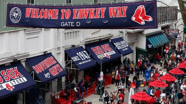 In this April 4, 2014 file photo, fans enjoy pre-game festivities along Yawkey Way outside Fenway Park in Boston. Boston Red Sox principal owner John Henry says he wants to take steps to rename all of Yawkey Way, a street that has been an enduring reminder of the franchise's complicated racial past.