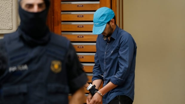 A suspect is led out of a building by police in Ripoll, north of Barcelona on Friday. Police arrested three people in the small town near the Pyrenees mountains and Spain's border with France in connection with the van attack in Barcelona that killed 13 and wounded dozens and a second attack in Cambrils.