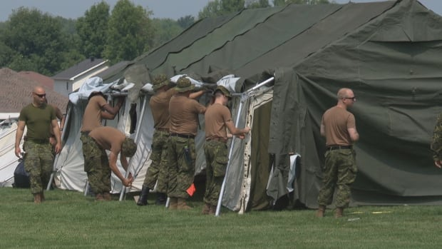 Members of the Royal Canadian Dragoons from CFB Petawawa set up tents on the Nav Centre grounds on Aug. 18, 2017. The tents can house upwards of 500 asylum seekers.