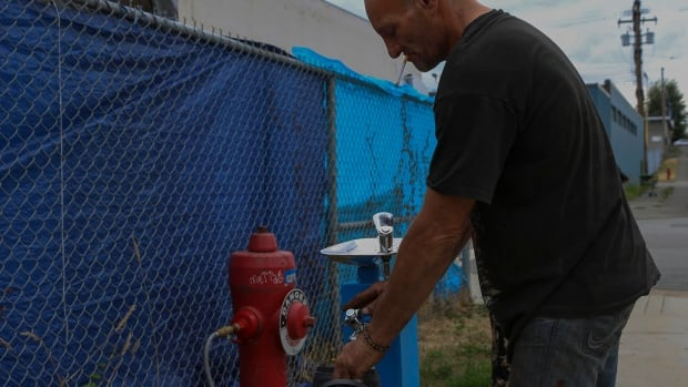 Sugar Mountain tent city resident Ward Ferguson says the newly installed water station is a huge improvement over hauling salvaged water from nearby businesses.