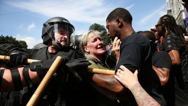 Protesters face off with riot police escorting conservative activists following a march in Boston against a planned 'Free Speech Rally.' It comes just one week after the violent 'Unite the Right' rally in Virginia left one woman dead and dozens more injured.