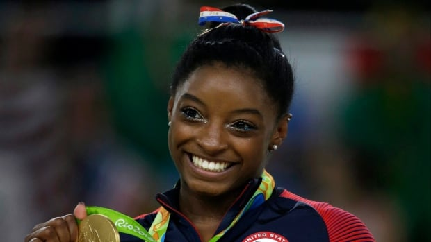 American Simone Biles displays her gold medal for the floor routine during the artistic gymnastics women's apparatus final at the 2016 Games in Rio last summer.
