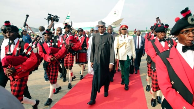 Nigerian President, Muhammadu Buhari, centre, walks down a red carpet after his arrival at the Nnamdi Azikiwe airport in Abuja, Nigeria, on Saturday.