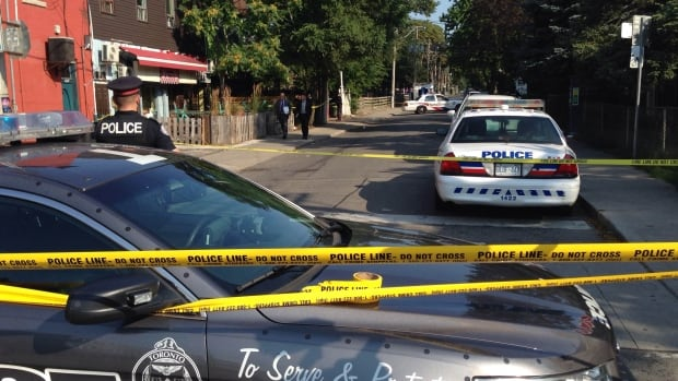 Toronto police investigate the scene near Bathurst and College Sunday.