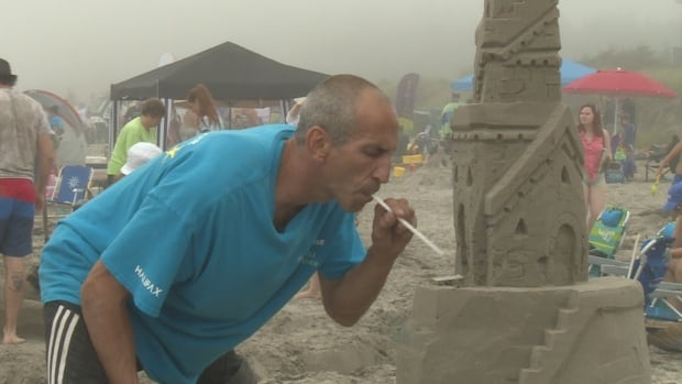 Shawn Gayton uses a straw to blow away tiny portions of sand and lines his buckets with wax so the sand slides out in one piece.