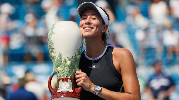 Garbine Muguruza, above, holds the Rookwood Cup after defeating Simona Halep 6-1, 6-0 in the women's singles final at the Western & Southern Open on Sunday afternoon.