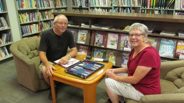 Dwayne and Irma Barkman play a game of Backgammon in the Melfort library during a tour stop.