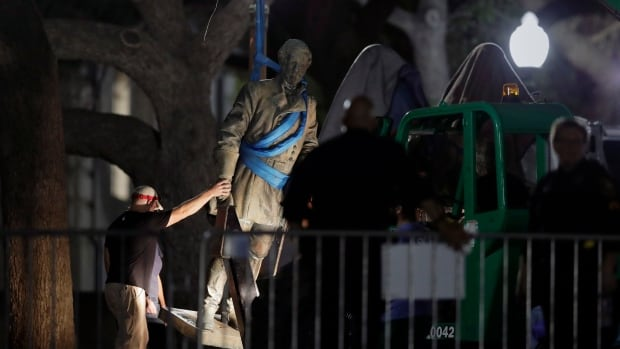 A statue of Confederate Gen. Robert E. Lee is removed from the University of Texas campus early Monday in Austin.