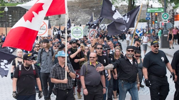 "Demonstrators of a right wing group, ""La Meute"" walk in silence to the legislature, Sunday, in Quebec City."