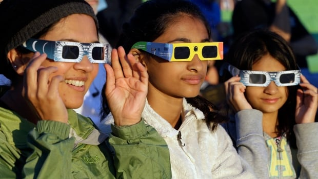 Seattle residents Schweta, Rhea and Saanvi Kulkarni, left to right, try out their eclipse glasses at a gathering of viewers in Salem, Ore., early Monday in preparation for the total solar eclipse.