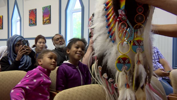 Canadian newcomers from the Saskatoon Open Door Society look at a Cree headdress on the Muskeg Lake Cree Nation.
