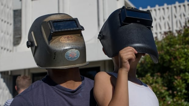 Eclipse watchers at the HR MacMillan Science Centre in Vancouver use welder masks to see the sun.