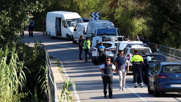 Catalan police vans are parked along a road near the place where Younes Abouyaaqoub, the man who drove the van that killed more than a dozen people in Barcelona last week, was killed by police in Subirats, Spain, on Monday.