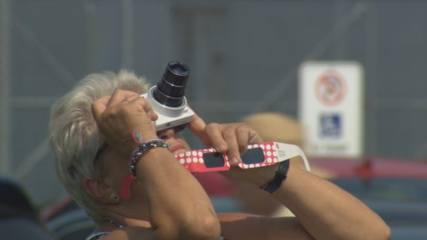 Many people were sporting a camera in one hand and a pair of eclipse glasses in the other.