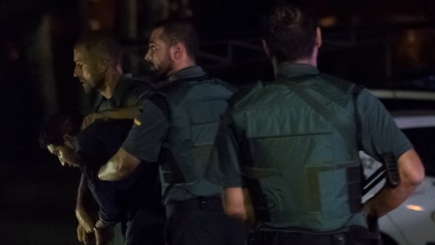 Spanish police officers escort one of four men accused of involvement in an Islamist cell behind a van attack in Barcelona last week.