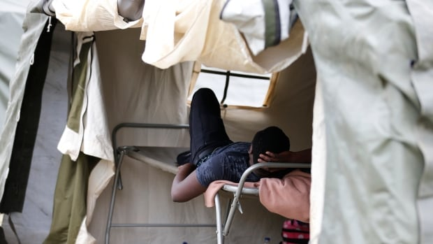 An asylum seeker rests in a tent at the Canada-United States border in Saint-Bernard-de-Lacolle, Que. A York University professor found a wide variation among Immigration and Refugee Board members in the number of refugee claims that were accepted.