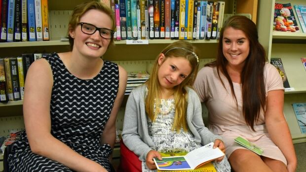 Tutor Ellie Beck (left), student Shaylyne Carver, and Ready, Set, Learn! co-ordinator Gina Hyson read their favourite books at the Stratford Public Library.