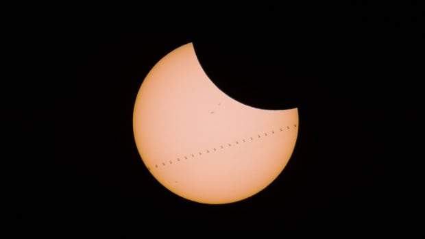 Derek Kind snapped this photo of the International Space Station trekking across the sun's face as the moon closed in from above during Monday's rare solar eclipse.