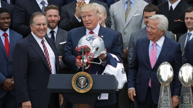 New England Patriots Head Coach Bill Belichick, left, and team owner Robert Kraft, right, present a football helmet to U.S. President Donald Trump during a celebration of the team's Super Bowl in April.
