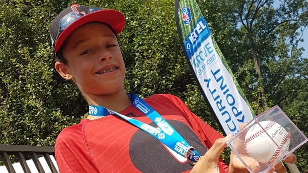 """Canada's Reece Usselman poses with the team's """"lucky ball"""" ahead Wednesday's quarter-final bout with Japan at the Little League World Series."""