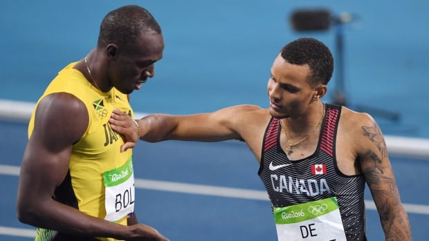 Andre De Grasse, right,  was unable to challenge Usain Bolt one last time after a hamstring injury forced him to withdraw from this year's world championships.
