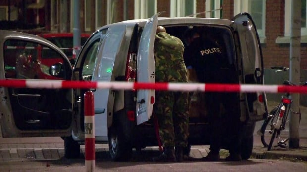 Police officers examine a van behind a cordoned-off area in Rotterdam, Wednesday, after a concert by rock band Allah-Las was cancelled Wednesday night following a threat, the city's mayor said. Police detained the driver of a van with Spanish license plates carrying a number of gas tanks inside.