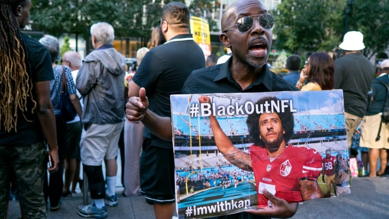 b33e48453 Eric Hamilton of New York joins others gathered in support of unsigned NFL  quarterback Colin Kaepernick on Wednesday in front of NFL headquarters in  New ...
