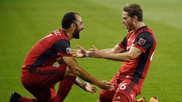 Toronto FC midfielder Nicolas Hasler, right, celebrates his goal against the Philadelphia Union with Victor Vazquez in Wednesday's 3-0 win.
