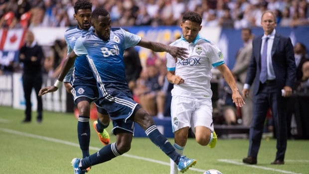Vancouver Whitecaps midfielder Tony Tchani, left, fights for control of the ball with Seattle Sounders midfielder Cristian Roldan, right, during the second half of Wednesday's 1-1 draw.