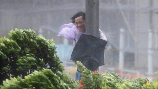 A man holds onto a lamp post against strong wind as Typhoon Hato hits Hong Kong.