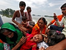A child reacts to the camera while sitting on his father's back as they make their way in a flooded area in Bogra, Bangladesh, on Aug. 20. More than eight million people in the country are affected by this summer's monsoon season floods.