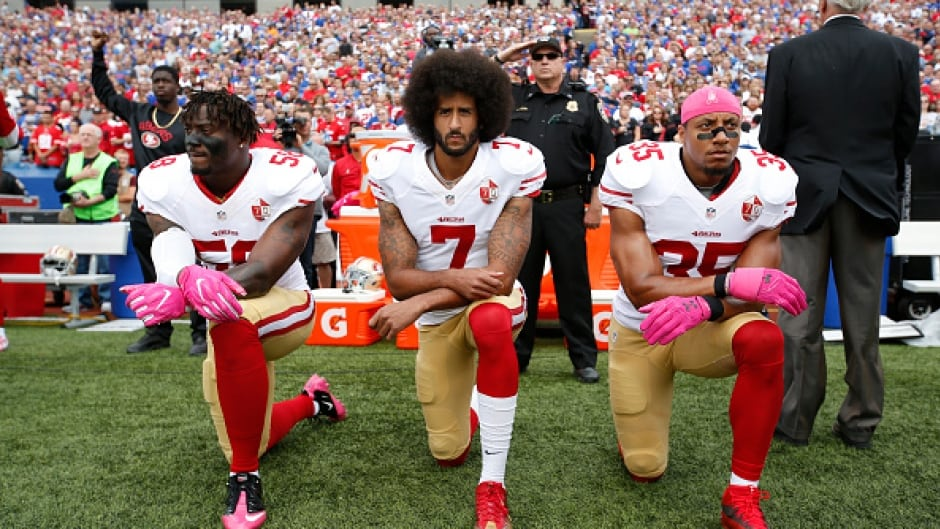 Eli Harold, Colin Kaepernick (centre) and Eric Reid of the San Francisco 49ers kneel in protest on the sideline during the national anthem at New Era Field in New York on October 16, 2016.