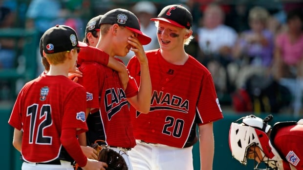 Canadian pitcher Reid Hefflick, left center, is comforted by teammates during a pitching change in the fourth inning against Reynosa, Mexico.