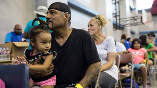 Caesar Mendez and his daughter Catalina wait inside the Corpus Christi Natatorium to board a bus to evacuate to San Antonio ahead of Hurricane Harvey on Thursday in Corpus Christi Texas