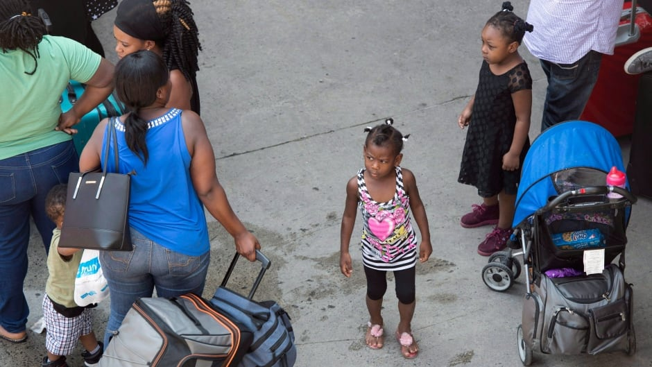 A young girl waits as asylum seekers line up to enter Olympic Stadium. The stadium is being used as temporary housing to deal with the influx of asylum seekers arriving from the United States.